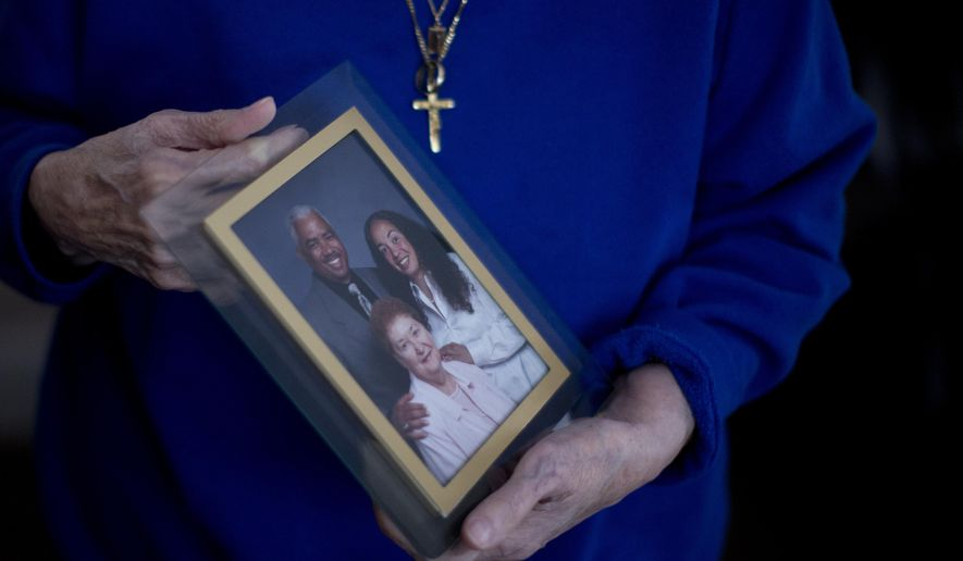 In this Jan. 11, 2017, photo, a person holds a photo of Karen Batts, pictured at right, in Oregon. Batts died of hypothermia in a parking garage in Portland, Ore. (Beth Nakamura/The Oregonian via AP)