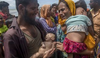 Rohingya Muslim man Naseer Ud Din holds his infant son Abdul Masood, who drowned when the boat they were traveling in capsized just before reaching the shore, as his wife Hanida Begum cries upon reaching the Bay of Bengal shore in Shah Porir Dwip, Bangladesh. Myanmar, a predominantly Buddhist nation of 60 million, was basking in international praise just a few years ago as it transitioned to democracy after a half-century of dictatorship. Since then, a campaign of killings, rape and arson attacks by security forces and Buddhist-aligned mobs have sent more than 850,000 of the country's 1.3 million Rohingya fleeing. (AP Photo/Dar Yasin, File)