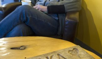 Guy Holt is shown at Coppa coffee shop in Juneau, Alaska, on Thursday, Dec. 14, 2017, with a carved plaque he found on Sandy Beach in Junuea 11 years ago. Holt has been trying to find the owner ever since. (Michael Penn/Juneau Empire via AP)