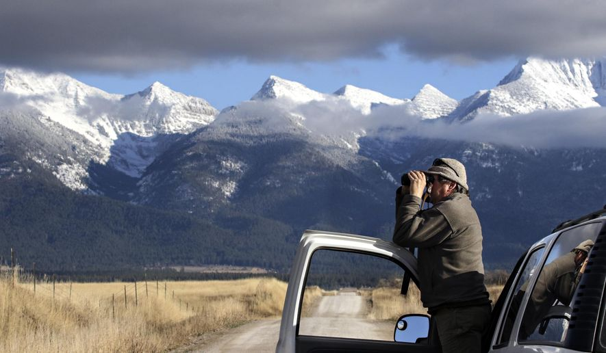 In this Dec. 6, 2017 photo,Denver Holt, founder of the 30-year-old nonprofit Owl Research Institute, peers through binoculars in search of a snowy owl near Charlo, Mont. (Greg Lindstrom/Flathead Beacon via AP)