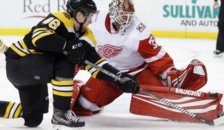 Detroit Red Wings' Jimmy Howard (35) blocks a shot by Boston Bruins' Matt Grzelcyk (48) during the second period of an NHL hockey game in Boston, Saturday, Dec. 23, 2017. (AP Photo/Michael Dwyer)