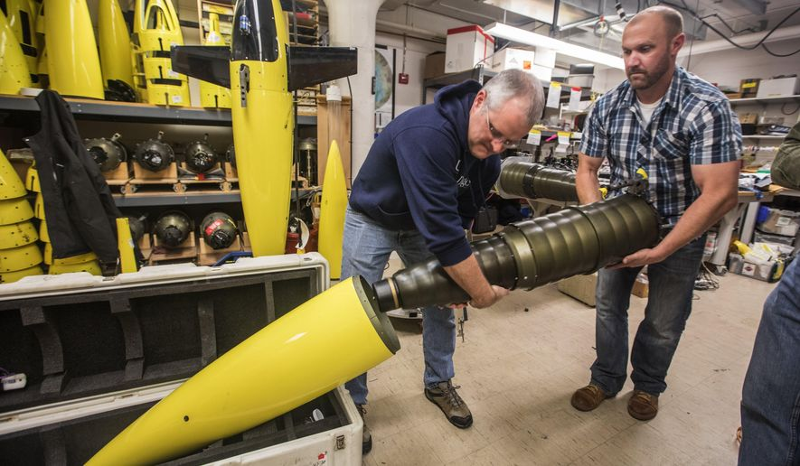 "In a Monday, Nov. 20, 2017 photo, University of Washington oceanographers Jason Gobat and Ben Jokinen load the ""pupa"" into the underwater fairing ""sea glider"" that will be used in an antarctic expedition to gather data under the sea ice sheets to estimate future melting and sea level rise.(Steve Ringman/The Seattle Times via AP)"