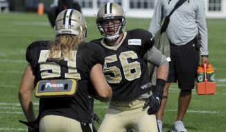 FILE - In this Aug. 15, 2016 file photo, New Orleans Saints outside linebacker Michael Mauti (56) works with linebacker Jeff Schoetter (51) in a drill during the NFL football teams training camp in White Sulphur Springs, W.Va.   Mauti became so fearful of food in recent years that even the thought of a holiday dinner gave him high anxiety. It took career-threatening surgeries and the removal of his large intestine to treat his case of ulcerative colitis. But Mauti has made an unlikely return to the field with in a years' time. Now he's helping the Saints' push for the playoffs and also trying to help others in all walks of life who've struggled with diseases similar to his.(AP Photo/Chris Tilley)