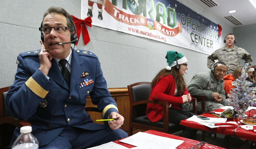 FILE - In this Dec. 24, 2014, file photo, Canadian Brig. Gen. Guy Hamel, NORAD and USNORTHCOM Deputy Director of Policy, Strategy, and Plans, joins other volunteers taking phone calls from children around the world asking where Santa is and when he will deliver presents to their homes, inside a phone-in center during the annual NORAD Tracks Santa Operation, at the North American Aerospace Defense Command, at Peterson Air Force Base, Colo. Hundreds of military and civilian volunteers at NORAD are estimated to field more than 100,000 calls this year throughout Christmas Eve, from children from all over the world eager to hear about Santa's progress. (AP Photo/Brennan Linsley, file)