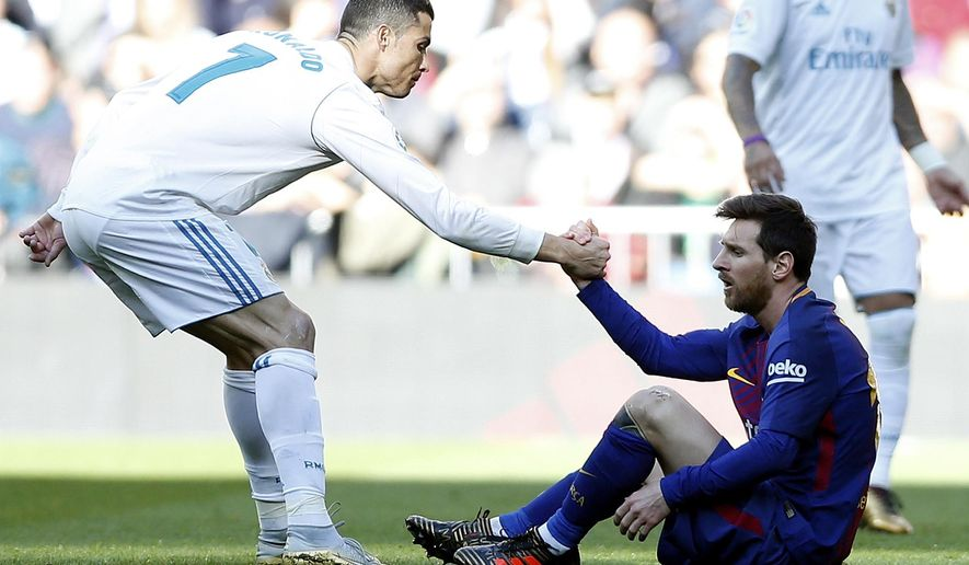 Real Madrid's Cristiano Ronaldo, left, helps Barcelona's Lionel Messi get back on his feet during the Spanish La Liga soccer match between Real Madrid and Barcelona at the Santiago Bernabeu stadium in Madrid, Spain, Saturday, Dec. 23, 2017. (AP Photo/Francisco Seco)