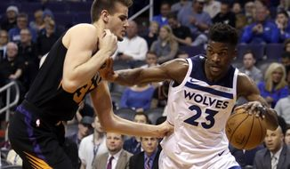 Minnesota Timberwolves guard Jimmy Butler (23) drives against Phoenix Suns forward Dragan Bender in the second quarter during an NBA basketball game, Saturday, Dec. 23, 2017, in Phoenix. (AP Photo/Rick Scuteri)