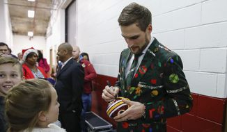 Wearing a holiday suit Washington Redskins quarterback Kirk Cousins signs autographs after an NFL football game against the Denver Broncos in Landover, Md., Sunday, Dec 24, 2017. The Redskins defeated the Broncos 27-11. (AP Photo/Alex Brandon)