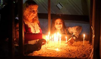 Iraqi Christians light candles before a Christmas Eve Mass in Our Lady of Salvation Church in Baghdad, Iraq, Sunday, Dec. 24, 2017. (AP Photo/Khalid Mohammed) ** FILE **