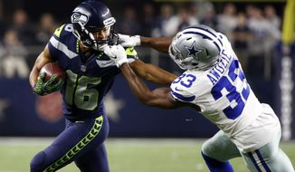 Seattle Seahawks wide receiver Tyler Lockett (16) carries the ball as his face masked is grabbed by Dallas Cowboys cornerback Chidobe Awuzie (33) in the second half of an NFL football game, Sunday, Dec. 24, 2017, in Arlington, Texas. (AP Photo/Michael Ainsworth)
