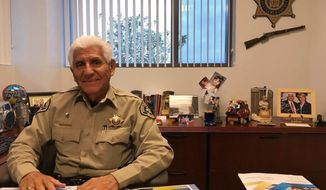 In this Dec. 5, 2017, photo, Santa Cruz County Sheriff Tony Estrada poses in his office in Nogales, Ariz. Estrada is a different kind of Arizona sheriff, one whose sensibility and opinions on immigration were shaped by being born in Mexico and immigrating with his family to the United States as a toddler. (AP Photo/Anita Snow)