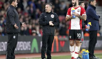 Southampton's Charlie Austin, right, argues with Huddersfield Town manager David Wagner, left, about goalkeeper Jonas Lossl's injury, during the English Premier League soccer match between Southampton and Huddersfied at St Mary's, in Southampton, England, Saturday, Dec. 23, 2017. (Adam Davy/PA via AP)