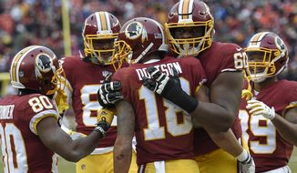 Washington Redskins wide receiver Josh Doctson (18) is congratulated by his teammates after scoring a touchdown during the second half an NFL football game against the Denver Broncos in Landover, Md., Sunday, Dec 24, 2017. (AP Photo/Nick Wass)