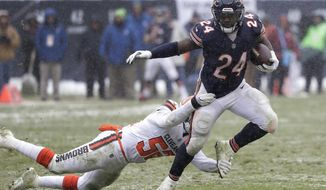 Chicago Bears running back Jordan Howard (24) tries to elude Cleveland Browns outside linebacker James Burgess (52) in the second half of an NFL football game in Chicago, Sunday, Dec. 24, 2017. (AP Photo/Charles Rex Arbogast)