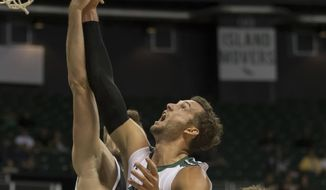 Davidson forward Will Magarity, left, and Hawaii forward Gibson Johnson, middle, go up for a rebound during the first half of an NCAA college basketball game at the Diamond Head Classic tournament, Saturday, Dec. 23, 2017, in Honolulu. (AP Photo/Eugene Tanner)