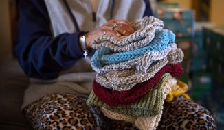 Phyllis Brown holds a stack of donated hats at the House of Bread and Peace in Evansville, Ind., on Wednesday, Dec. 13, 2017.  (Marlena Sloss /Evansville Courier & Press via AP)