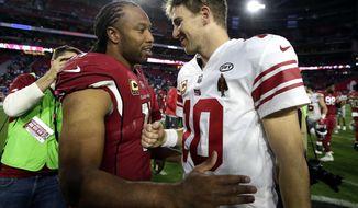 New York Giants quarterback Eli Manning (10) and Arizona Cardinals wide receiver Larry Fitzgerald (11) meet after an NFL football game, Sunday, Dec. 24, 2017, in Glendale, Ariz. The Cardinals won 23-0. (AP Photo/Rick Scuteri)