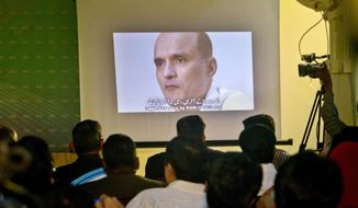 FILE - In this March 29, 2016, file photo, journalists look a image of Indian naval officer Kulbhushan Jadhav, who was arrested in March 2016, during a press conference by Pakistan's army spokesman and the Information Minister, in Islamabad, Pakistan. Pakistan's foreign ministry said on Sunday, Dec. 24, 2017, New Delhi has officially informed Islamabad that the wife and mother of Jadhav, who faces death penalty for espionage and sabotage are arriving in the capital for a meeting with him. (AP Photo/Anjum Naveed, File)