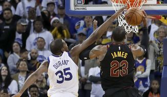 Golden State Warriors forward Kevin Durant (35) blocks Cleveland Cavaliers forward LeBron James (23) shot during the second half of an NBA basketball game in Oakland, Calif., Monday, Dec. 25, 2017. The Warriors won 99-92. (AP Photo/Tony Avelar)