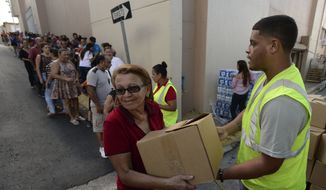 In this Dec. 21, 2017 photo, Doris Martinez receives supplies and water from municipal staff outside the City Hall in Morovis, Puerto Rico. Over 30,000 residents of that mountain town wait for the restoration of electric power service, one of the last municipalities of Puerto Rico that remains completely in the dark more than three months after the passage of Hurricane Maria. (AP Photo/Carlos Giusti) **FILE**