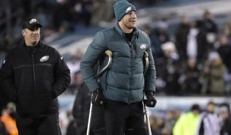 Philadelphia Eagles' Carson Wentz, right, walks with head coach Doug Pederson before an NFL football game against the Oakland Raiders, Monday, Dec. 25, 2017, in Philadelphia. (AP Photo/Michael Perez)