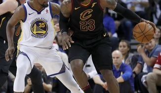 Cleveland Cavaliers forward LeBron James (23) moves the ball around Golden State Warriors forward Kevin Durant (35) during the second half of an NBA basketball game in Oakland, Calif., Monday, Dec. 25, 2017. The Warriors won 99-92. (AP Photo/Tony Avelar)