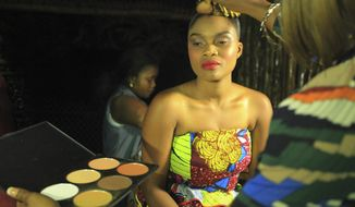 In this photo taken Saturday Dec. 23, 2017, A model makeup back stage before a fashion show in Beni Eastern Congo . Young Congolese designer Miki Sikabwe has trained in Rwanda, Burundi and Kenya, but hasn't gotten the chance to show her work locally in eastern Congo for years because of insecurity. (AP Photo/Al-Hadji Kudra Maliro)