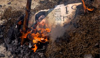 Shiite Muslims burned an effigy of Abu Bakr al-Baghdadi in June, but many enemies of the Islamic State group don't think its leader has gone to the ash heap of history just yet. (Associated Press)