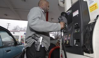 """In a Jan. 12, 2012 photo, Rick Ector carries his Smith and Wesson 9mm as he prepares to pump gas in Detroit. Ector is pushing to make Detroit an """"open carry"""" city and organizes public dinners and picnics where each legally licensed attendee wears a handgun. (Associated Press) **FILE**"""