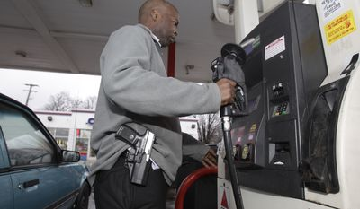 "In a Jan. 12, 2012 photo, Rick Ector carries his Smith and Wesson 9mm as he prepares to pump gas in Detroit. Ector is pushing to make Detroit an ""open carry"" city and organizes public dinners and picnics where each legally licensed attendee wears a handgun. (Associated Press) **FILE**"