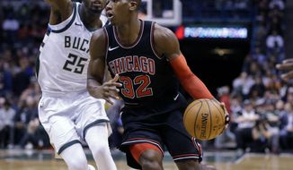 Chicago Bulls' Kris Dunn, right, drives past Milwaukee Bucks' DeAndre Liggins during the first half of an NBA basketball game, Tuesday, Dec. 26, 2017, in Milwaukee. (AP Photo/Jeffrey Phelps)