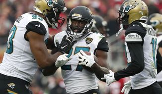 Jacksonville Jaguars running back Leonard Fournette, center, celebrates with Calais Campbell, left, and Dede Westbrook after scoring a touchdown against the San Francisco 49ers during the first half of an NFL football game in Santa Clara, Calif., Sunday, Dec. 24, 2017. (AP Photo/Tony Avelar)