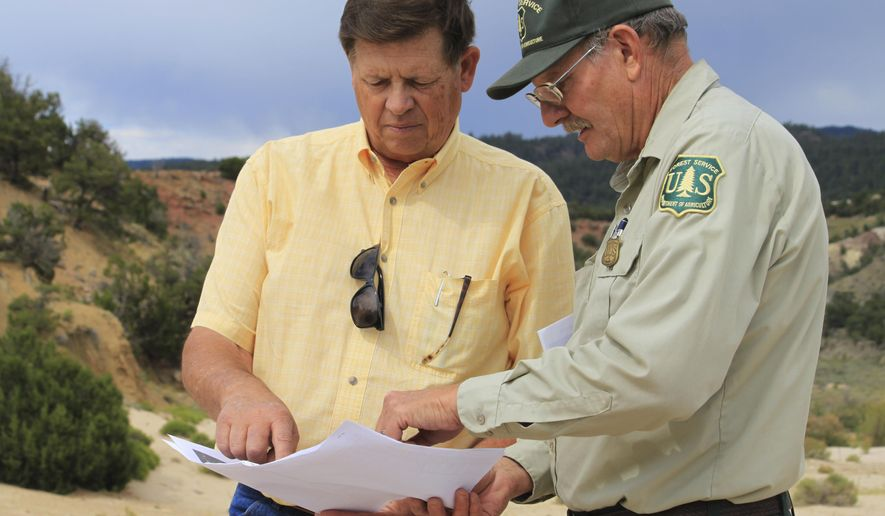In this July 17, 2017 photo, New Mexico Land Commissioner Aubrey Dunn, left, and Larry Gore with the U.S. Forest Service look at survey maps of the Nacimiento Copper Mine near Cuba, N.M., as they discuss tailing piles and contaminated groundwater at the site. Dunn has hired a consultant to review the site and determine what options exist for cleaning up tons of tailings made up of waste from past mining operations. The mine is among many sites in the West that are in need of remediation. (AP Photo/Susan Montoya Bryan)