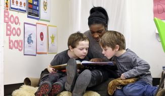 "In this photo taken Feb. 12, 2016, assistant teacher D'onna Hartman, reads to Frederick Frenious, left, and Gus Saunders at the Creative Kids Learning Center, a school that focuses on pre-kindergarten for 4- and 5-year-olds, in Seattle. Hartman used the ""boo boo bag"" corner to settle the two down after a small altercation left one in tears. In perhaps an unexpected twist, historically conservative strongholds like Oklahoma and West Virginia are leading efforts to bring preschool to all and Alabama and Georgia are also red states that have notable programs. But some liberal leaning-cities like Seattle and New York also are running public pre-K programs. (AP Photo/Elaine Thompson, File)"