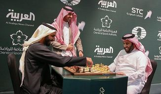 In this Monday, Dec. 25, 2017, photo released by Saudi Press Agency, two Saudi officials play chess during the opening the first ever chess tournament in Riyadh. Saudi Arabia is hosting a world chess tournament for the first time on Tuesday nearly two years after the country's top cleric issued a religious edict against playing the board game. (Saudi Press Agency via AP)