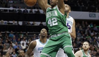 Boston Celtics' Al Horford (42) dunks past Charlotte Hornets' Nicolas Batum (5) during the first half of an NBA basketball game in Charlotte, N.C., Wednesday, Dec. 27, 2017. (AP Photo/Chuck Burton)