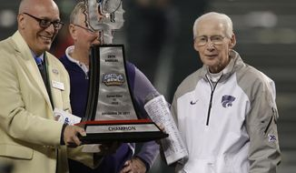 Kansas State head coach Bill Snyder, right, accepts the trophy after defeating UCLA 35-17 during an NCAA college football Cactus Bowl game, Tuesday, Dec. 26, 2017, in Phoenix. (AP Photo/Rick Scuteri)