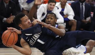 Villanova's Jalen Brunson tries to keep the ball from DePaul's Brandon Cyrus during the first half of an NCAA college basketball game Wednesday, Dec. 27, 2017, in Chicago. (AP Photo/Jim Young)
