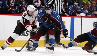 Colorado Avalanche center Carl Soderberg (34), of Sweden, reaches out to control the puck as Arizona Coyotes defenseman Luke Schenn covers in the second period of an NHL hockey game Wednesday, Dec. 27, 2017, in Denver. (AP Photo/David Zalubowski)