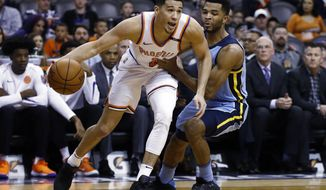 Back from injury, Phoenix Suns guard Devin Booker (1) dribbles past Memphis Grizzlies guard Andrew Harrison, right, during the first half of an NBA basketball game, Tuesday, Dec. 26, 2017, in Phoenix. (AP Photo/Ross D. Franklin)