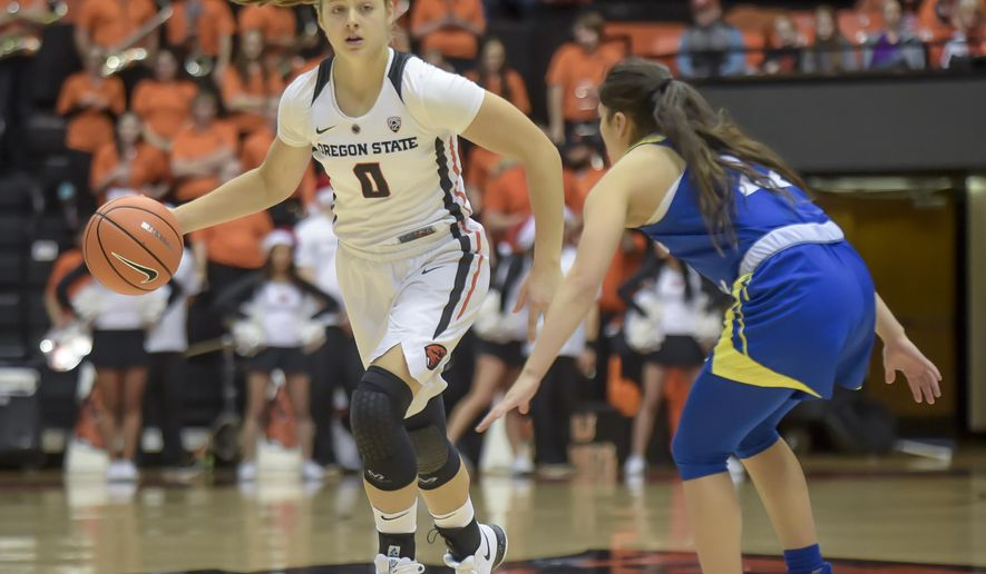 This photo taken Dec. 10, 2017, shows Oregon State guard Mikayla Pivec, left, bringing the ball upcourt against San Jose State's Danae Marquez during an NCAA college basketball game Corvallis, Ore.  Pivec was unsure of the reaction she'd get when she approached Oregon State coach Scott Rueck last spring about possibly joining the track team. Lots of athletes run track in the offseason to help them stay sharp, but Pivec was a bit unusual in that she wanted to moonlight as a javelin thrower. Rueck agreed, albeit with a caveat: The javelin couldn't take the place of hoops.  (Andy Cripe/The Corvallis Gazette-Times via AP)