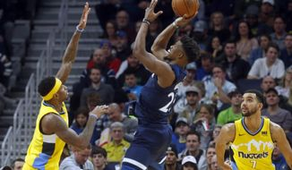 Minnesota Timberwolves' Jimmy Butler, center, shoots over Denver Nuggets' Torrey Craig, left, in the second half of an NBA basketball game Wednesday, Dec. 27, 2017, in Minneapolis. The Timberwolves won 128-125. Butler led the Timberwolves with 39 points. (AP Photo/Jim Mone)