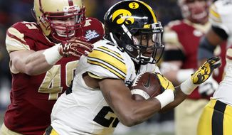 Boston College linebacker Kevin Bletzer (49) prepares to tackle Iowa running back Akrum Wadley (25) who runs with the ball during the first quarter of the Pinstripe Bowl NCAA college football game, Wednesday, Dec. 27, 2017, in New York. (AP Photo/Kathy Willens)