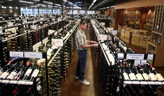 FILE- In this June 30, 2017, file photo, a worker at a state liquor store changes prices on wine, liquor and higher-alcohol beer, after closing to the public near downtown Salt Lake City. One of the world's biggest brewing companies says it may stop creating weak beer that can be sold at Utah grocery and convenience stores where stronger beer, wine and liquor sales are forbidden. (AP Photo/Rick Bowmer, File)