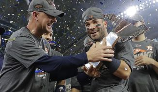 FILE - In this Oct. 21, 2017, file photo, Houston Astros manager A.J. Hinch and Jose Altuve hold the championship trophy after Game 7 of baseball's American League Championship Series against the New York Yankees, in Houston. Altuve was named The Associated Press Male Athlete of the Year on Wednesday, Dec. 27, 2017. (AP Photo/David J. Phillip, File)