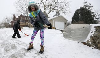 Karlee Winter, right, 11, and her brother Samuel Espinoza, 8, shovel snow from their neighbor's sidewalk in Dubuque, Iowa, on Thursday, Dec. 28, 2017. (Nicki Kohl/Telegraph Herald via AP)