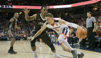 File- This Dec. 2, 2017, file photo shows Virginia's Kyle Guy (5) driving around Lehigh's Lance Tejada (5) during the first half of an NCAA college basketball game in Charlottesville, Va. The sophomore guard is leading the ninth-ranked Cavaliers in scoring entering Saturday's ACC opener against Boston College. (AP Photo/Lee Luther Jr., File) **FILE**