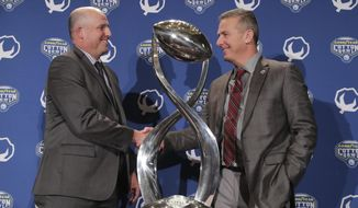 Southern California head coach Clay Helton, left, and Ohio State head coach Urban Meyer shake hands and pose for photos after a news conference for the Cotton Bowl NCAA college football game in Dallas, Thursday, Dec. 28, 2017. The game is scheduled for Friday, Dec. 29, 2017, in Arlington, Texas. (AP Photo/LM Otero)
