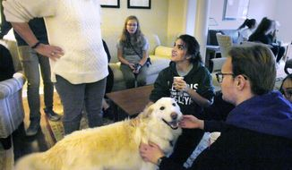 """In this Dec. 13, 2017 photo, Elizabeth Jensen, left, wife of Illinois Wesleyan University  President Eric Jensen, brought her """"First Dog"""" named Calvin to meet Gabrielle Ghaderi, an undecided freshman, and Matthew Humason, a freshman acting major, during """"Barks and Beverages Break"""" at Jensen's home on the IWU campus in Bloomington, Illinois. The dog has become a popular distraction for students at IWU. (David Proeber, The Pantgraph via AP)"""