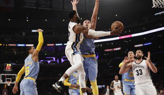 Memphis Grizzlies' Tyreke Evans, center left, passes the ball to Marc Gasol, right, as he is pressured by Los Angeles Lakers' Larry Nance Jr. during the first half of an NBA basketball game Wednesday, Dec. 27, 2017, in Los Angeles. (AP Photo/Jae C. Hong)