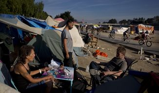 David Pirate, from left, Richard Ramirez, and Eric Koehler, who are homeless, pass time outside their tents after emptying a bottle of vodka as a group of cyclists ride along the Santa Ana River trail Saturday, Dec. 2, 2017, in Anaheim, Calif. Advocates say the homeless population has become more visible as police have cracked down on rules barring camping, driving people from parks and bus benches to a few centralized locations, such as the flood control channel along the Santa Ana River in Anaheim. (AP Photo/Jae C. Hong)